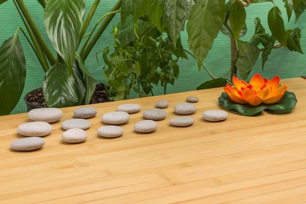 キャンドルとスパの石、緑の葉とオレンジ色のユリ。コンセプトをリラックス。木製の背景