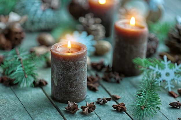Candle, anise stars and fir tree branch on wooden table, close up view