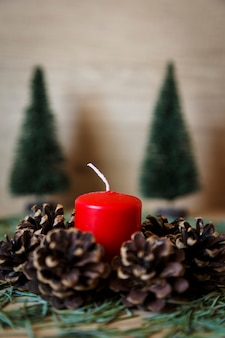 Candle beside a set of pine cones and spruce as christmas decoration