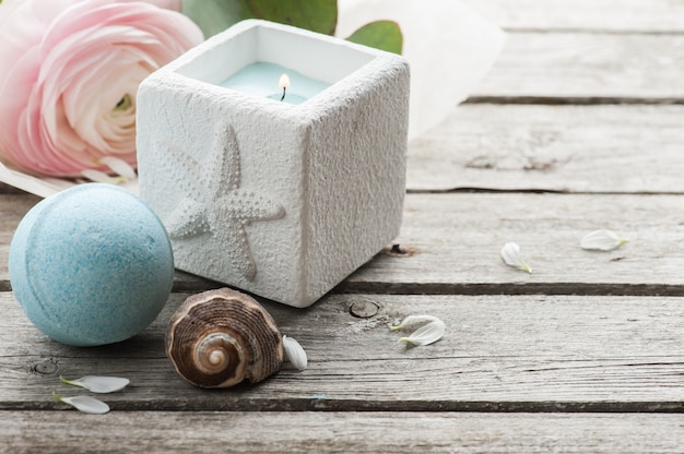 Candle and blue bath bomb over shabby wooden table