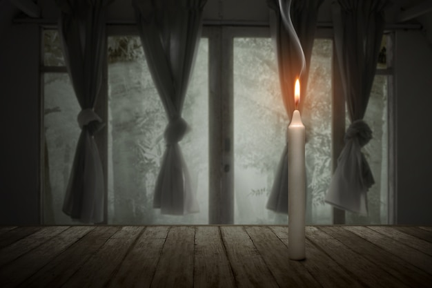 A candle burning in an abandoned house halloween concept