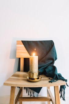 Candle in candlestick on wooden chair