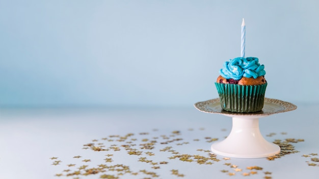 Candle on cupcake over the cakestand against blue background