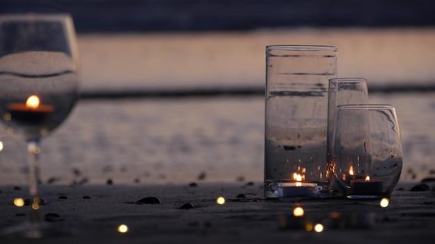 유리에 촛불 불꽃 조명, 캘리포니아 파도에 의한 낭만적인 해변 데이트, 여름 바닷물. 촛불 원활한 반복 시네마그래프. 와인 글라스, 모래 위의 와인용 유리. 아늑한 라운지 화환, 일몰.