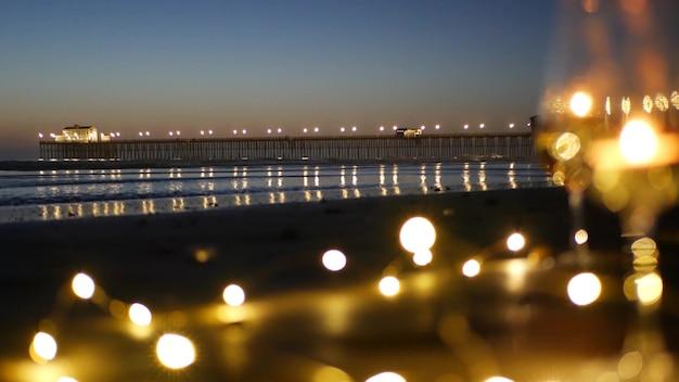 유리에 촛불 불꽃, 파도에 의한 낭만적인 해변 데이트, 여름 바다. 모래에 촛불입니다.