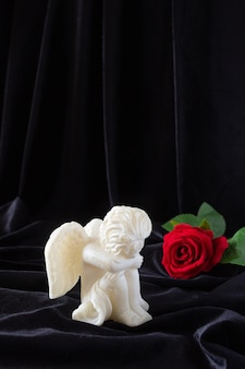 A candle in the form of an angel with wings and a red rose on a black cloth