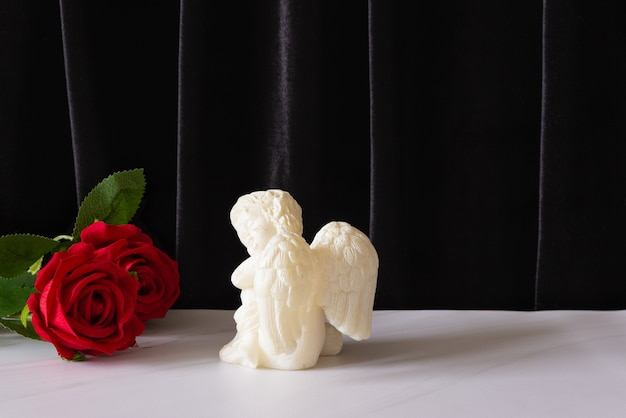 A candle in the form of an angel with wings and a red rose