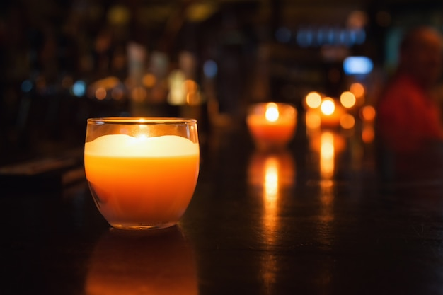 Candle in a glass. photos of cafe or restaurant reception. selective focus with bokeh