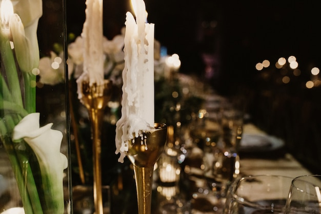 Candle in golden candlestick on wedding table