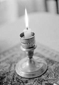 Candle holder with burning candle, close-up (b&w)