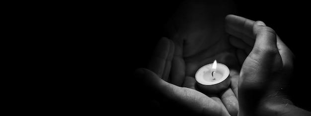 검은 배경에 불타는 손에 촛불.
