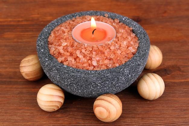 나무에 해양 소금 돌 그릇에 촛불
