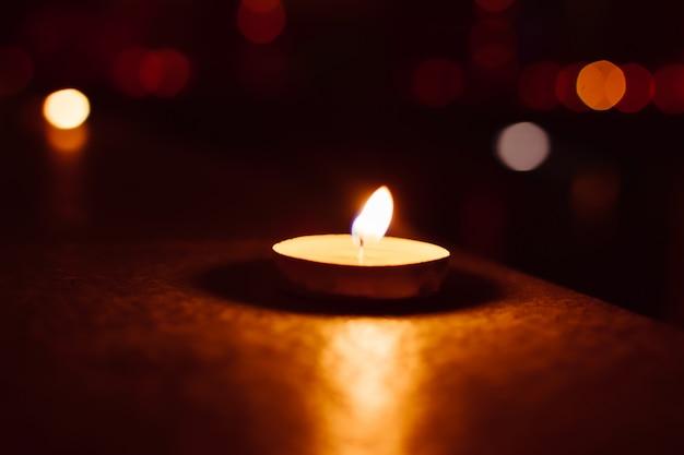 Свеча в темноте с фоном боке.