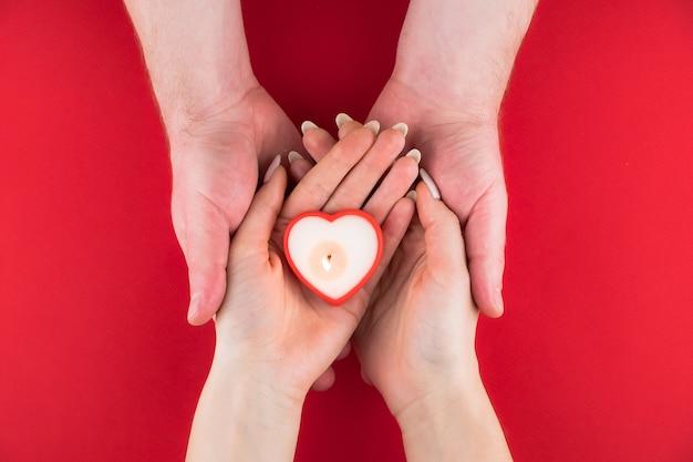 バレンタインデーのための赤い表面のカップルの手でハートの形をしたキャンドル