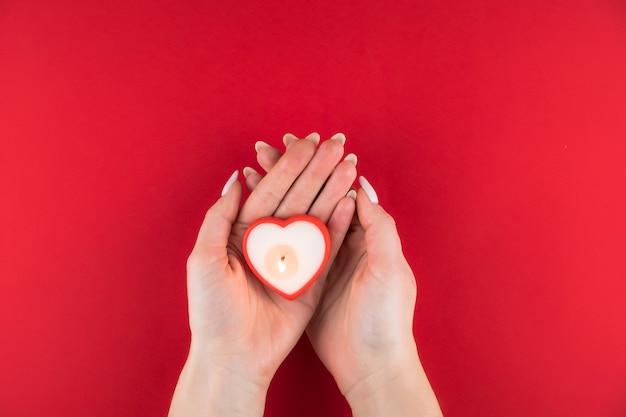 バレンタインの日の赤い表面に女性の手でハートの形をしたキャンドル。