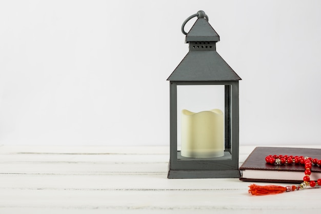 Candle in lantern holder; holy kuran book and red prayer beads on wooden desk against white backdrop