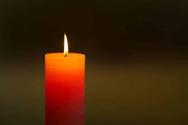 어두운 부드러운 배경에 불꽃이 있는 촛불