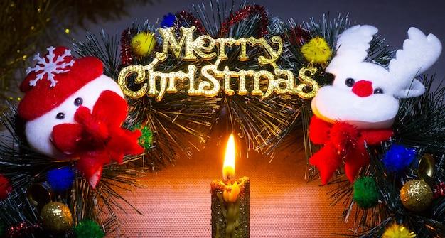 キャンドルは、メリークリスマスの碑文で伝統的なクリスマスリースを照らします_