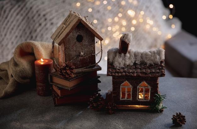 キャンドル。ガーランドライトで灰色と白の背景に分離された家のミニチュア。居心地の良い夜、雪と花輪のライト。家庭的な雰囲気、ロマンチックな日付、クリスマスまたは新年の概念