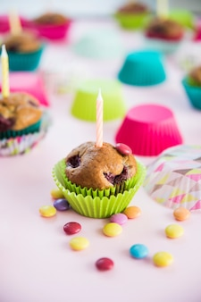 Candle on muffin with colorful candies on pink background