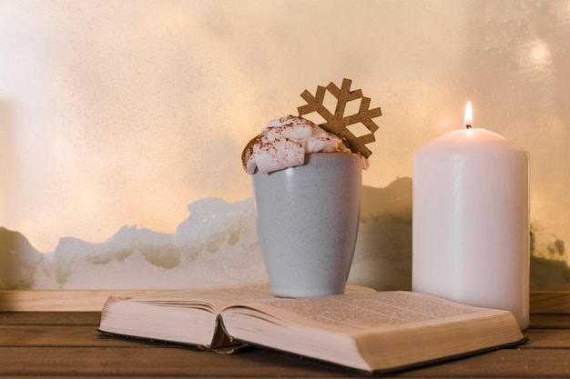 Candle near book and cup with toy snowflake on wood board near heap of snow through window