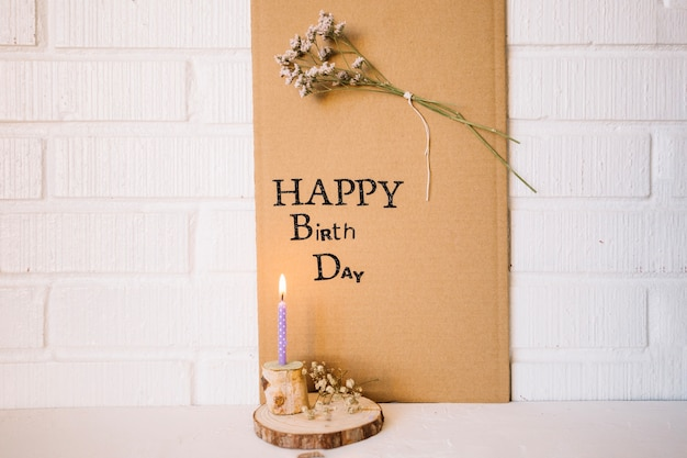Свеча возле картона с приветствием и цветком