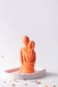 白い背景の上の男性と女性の抱擁のキャンドル。