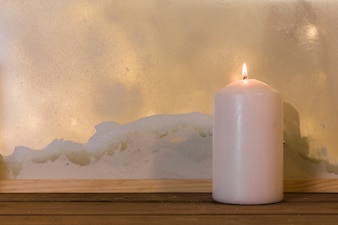 Candle on wood board near heap of snow through window