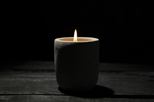 Свеча на деревянном столе против черного