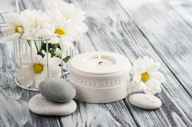 Candle and stones on wooden background