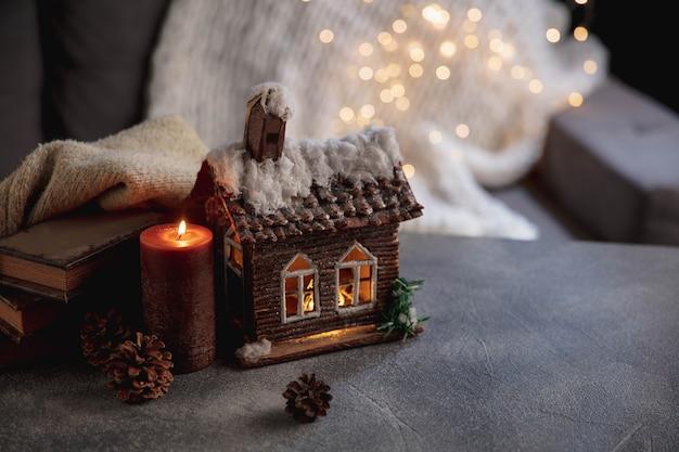 キャンドル。冬の家のミニチュアが照らされ、灰色と白の背景に本。居心地の良い夜、雪と花輪のライト。家庭的な雰囲気、ロマンチックな日付、クリスマスまたは新年の概念