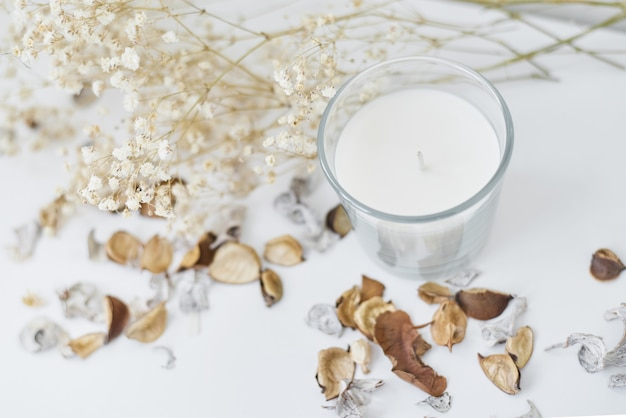 Candle with floral decor on a white table