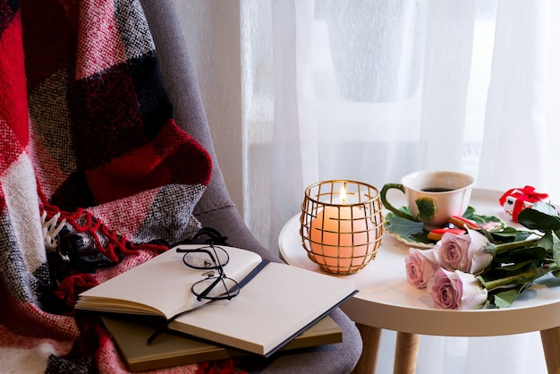 A candle with a notebook on a table with pink roses in a box near a window with a chair, a plaid and a book