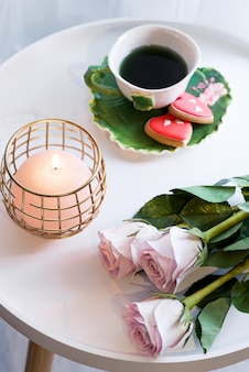 A candle with pink roses and cup of tea on white table