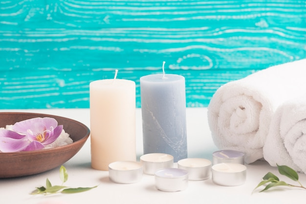 Candle with rolled up towel and spa slat with orchid flower on desk