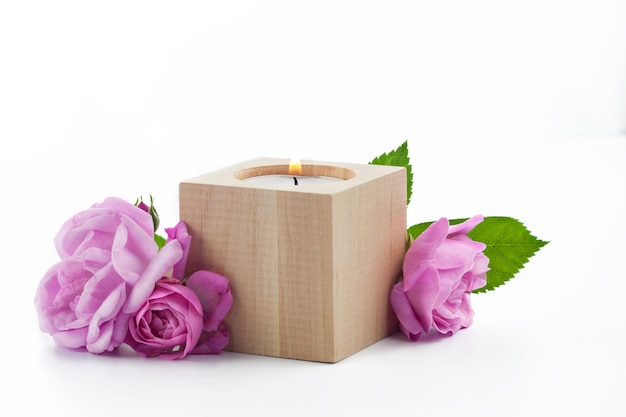 Candle in a wooden candle holder and bouquet of wild pink roses isolated on white surface