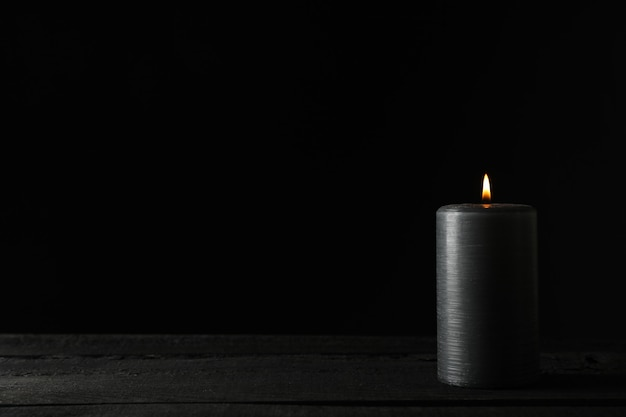 Candle on wooden table against black