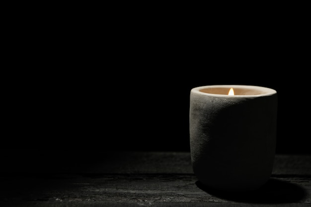 Candle on wooden table on black