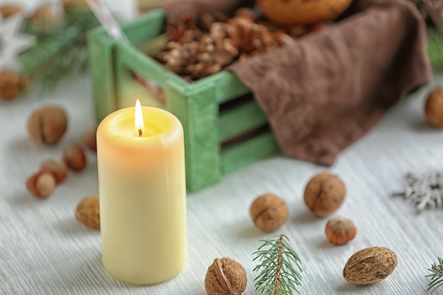 Candle on wooden table with nuts and wooden box