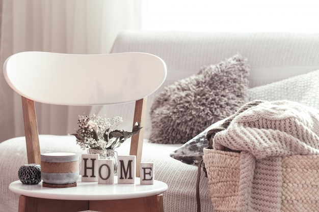 キャンドル、白い木製の椅子に家の木製の文字が付いている花が付いているつぼ。バックグラウンドにクッションが付いたソファと籐のバスケット。