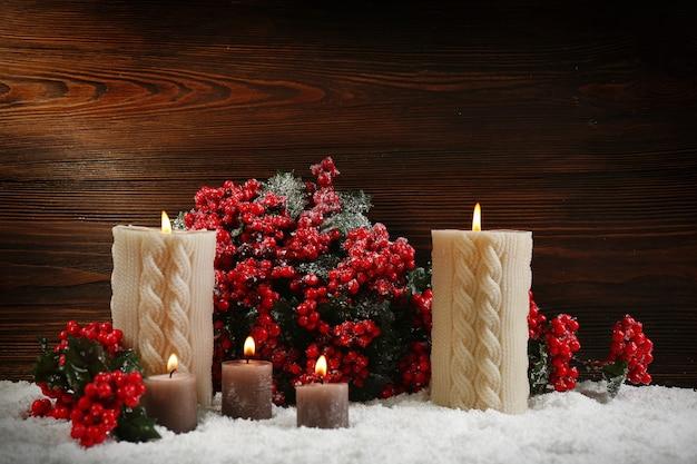 木の表面の雪の中でキャンドルとヒイラギの果実の枝、静物