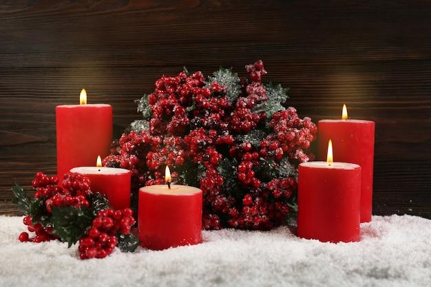 木の表面の雪の中でキャンドルとヒイラギの果実の枝