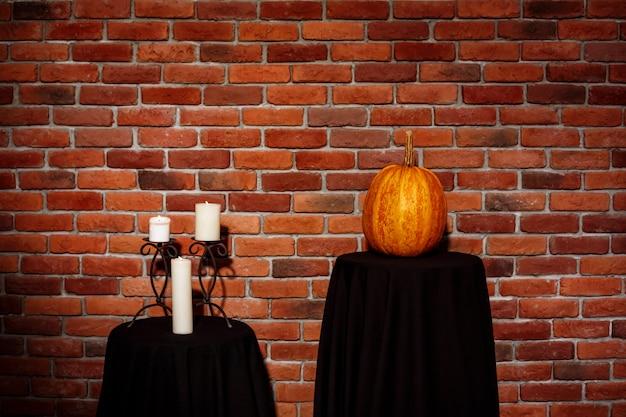 キャンドルとカボチャのレンガの壁の上のテーブル。ハロウィン。コピースペース。