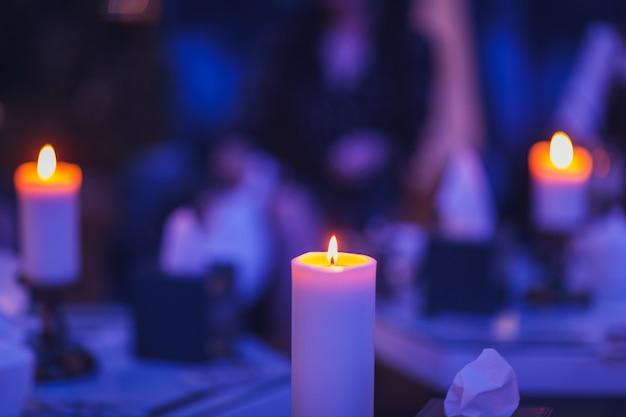 暗い青みがかった背景のキャンドルスタンドでキャンドルが燃えています