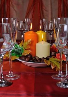 紅葉の栗とテーブルセッティングの一部としてのキャンドル