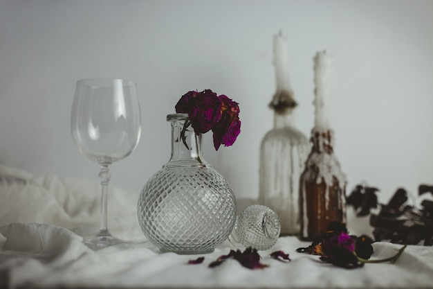 Candles on the bottles next to a vase with a flower inside and a glass