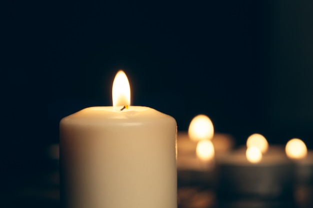 Candles burning in darkness over black