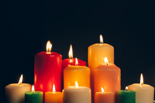 Candles burning in darkness over black,