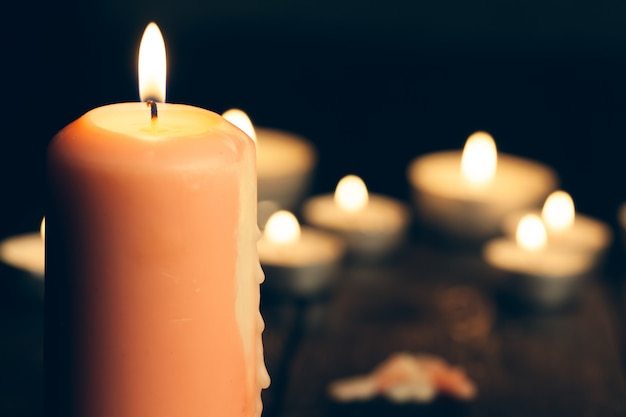 Candles burning in darkness over black.