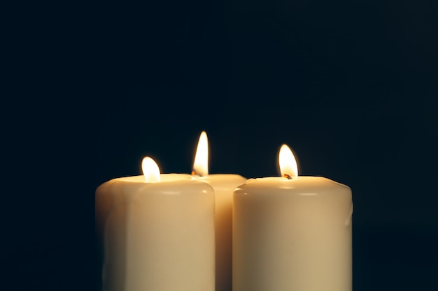 Candles burning in darkness. commemoration concept.